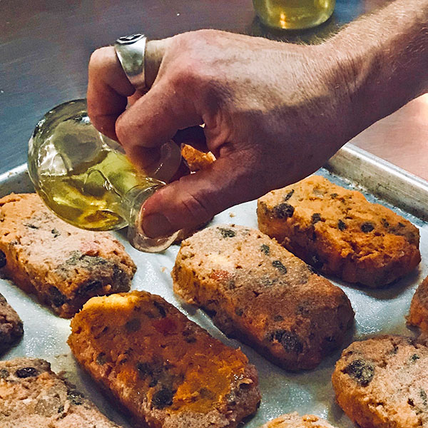 chef drizzling olive oil over fish cakes